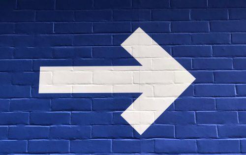Valkoinen nuoli sinisellä pohjalla